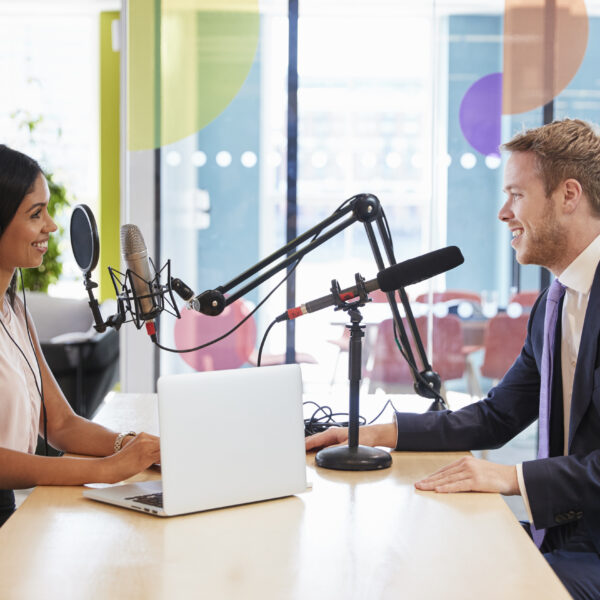 young-woman-interviewing-a-guest-in-a-studio-for-a-podcast