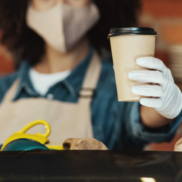 coffee-shop-worker-offering-takeout-drink