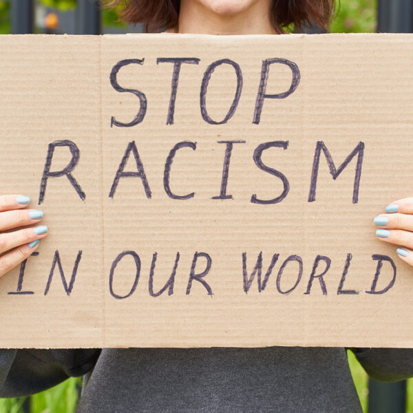 white-person-holds-sign-about-ending-racism