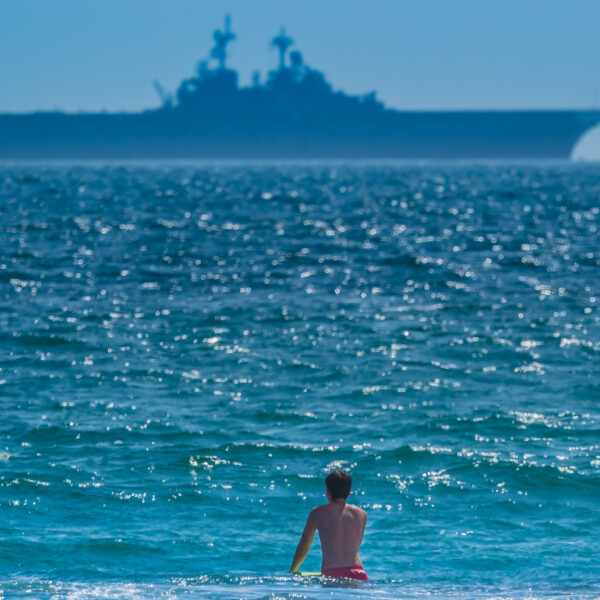 boy-wading-in-the-sea-looking-at-the-silhouette-of-ship